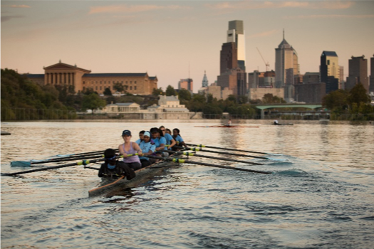 Girls rowing with skyline in background