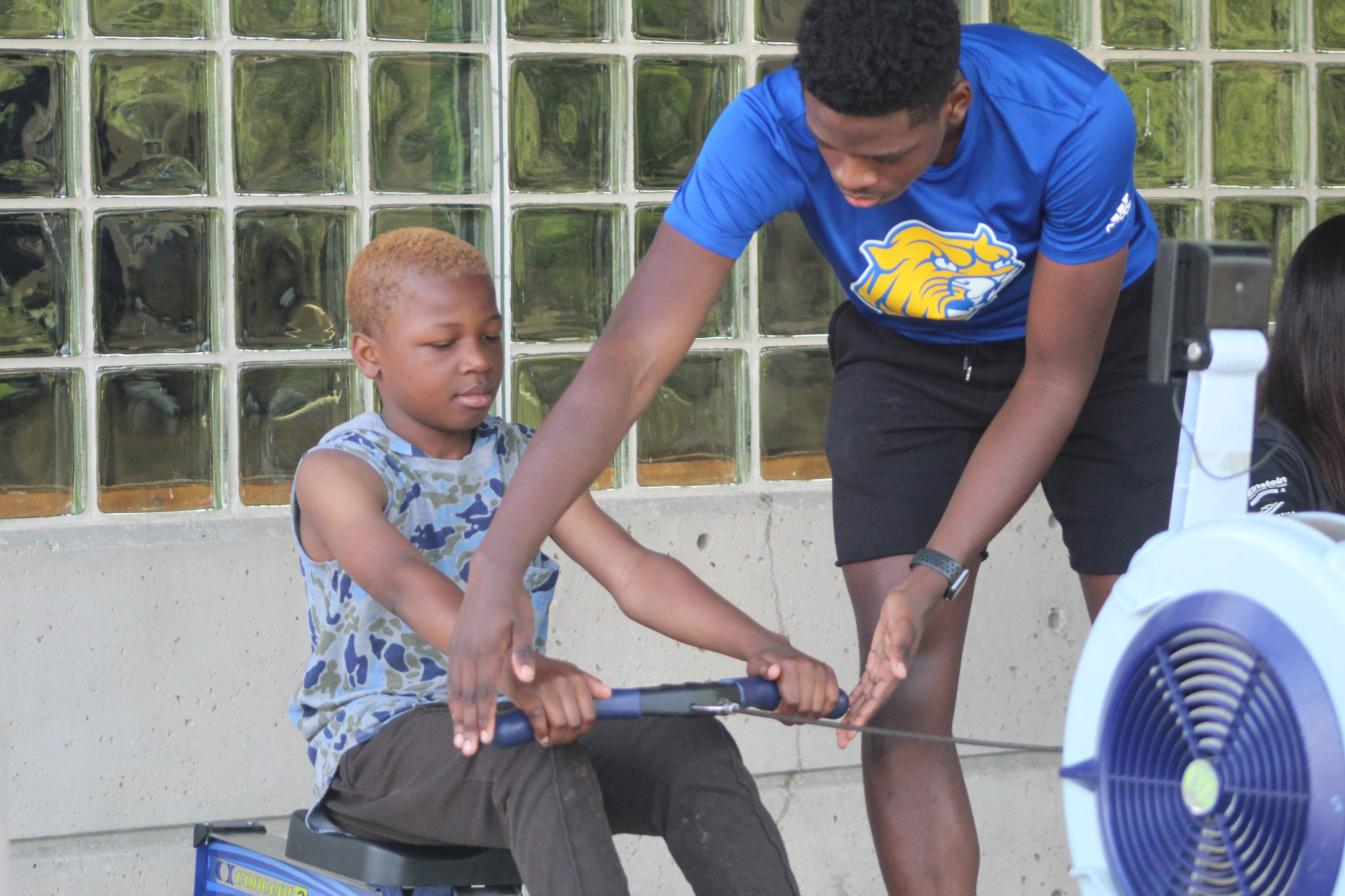 PCR Coach helping Middle Schooler on erg